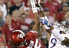 Oklahoma running back Joe Mixon (25) works to make a catch as Kansas safety Fish Smithson (9) defends during the first half of an NCAA college football game in Norman, Okla., Saturday, Oct.29, 2016.