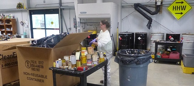 "Lydia Gibson, specialist, sorts items brought to the Lawrence-Douglas County Household Hazardous Waste Center. The center is now in one of its busy ""move-out"" months when residents get rid of household hazardous waste before moving from their homes."