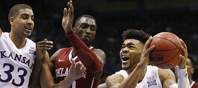 Kansas guard Frank Mason III (0) gets in for a bucket past Oklahoma forward Khadeem Lattin (12) during the second half, Monday, Feb. 27, 2017 at Allen Fieldhouse. At left is Kansas forward Landen Lucas (33).