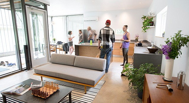 Students converse within the living area and kitchen space at the new Studio 804 house located at 1330 Brook St. in Lawrence on Wednesday, May 10, 2017.