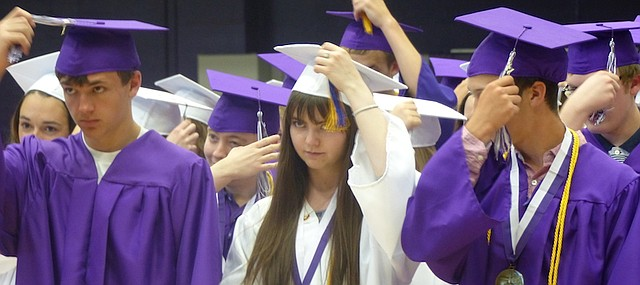Baldwin High School Class of 2017 members Cameron Burns, left, Elizabeth Brungardt and Noah Buckley move the tassels on their graduation caps from right to left, signifying their new status as graduates of the high school.