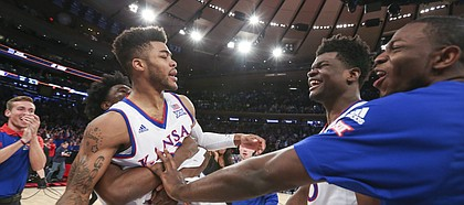 Kansas guard Frank Mason III (0) is hoisted up by teammate Josh Jackson as he is congratulated by center Udoka Azubuike and forward Dwight Coleby after Mason hit the game-winning shot to beat Duke 77-75 during the Champions Classic on Tuesday, Nov. 15, 2016 at Madison Square Garden in New York.