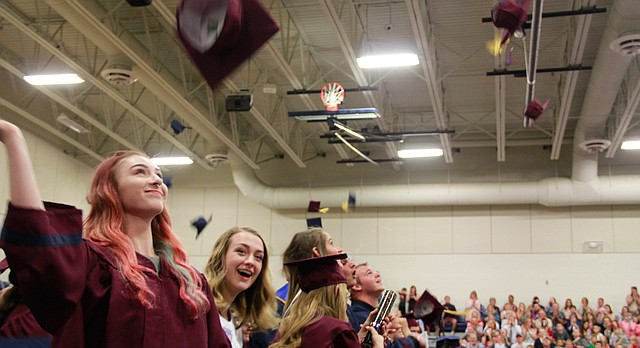 Eudora High School Graduate Emma Schmidt (left) throws her cap into the air on May 13, 2017, surrounded by fellow graduates. The ceremony was held in Eudora High School's gymnasium.