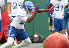 Kansas linebacker Kyron Johnson sweeps aside an obstacle during spring football practice on Tuesday, March 28, 2017.