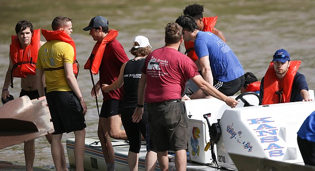 Rowers step off of a University of Kansas boat after being rescued from the bank of the Kansas River near the KU boathouse, Wednesday, May 17, 2017.