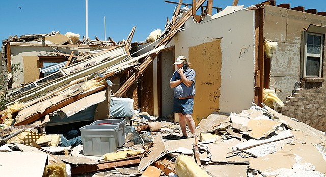 Jody Darling, a friend of the residents of this home in Elk City, Okla., talks on a phone while standing in a room of the house that is now totally exposed on Wednesday, May 17, 2017. Over a dozen tornadoes were reportedly spawned by powerful storms that raced through a swath of the central U.S. stretching from Texas to the Great Lakes on Tuesday evening. (Jim Beckel/The Oklahoman via AP)
