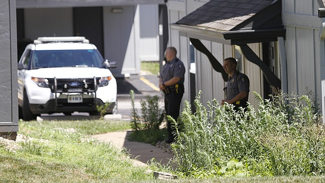 In this file photo from July 7, 2016, law enforcement officers stand guard at an apartment complex in the 2500 block of West Sixth Street, where police say an infant was found in a trash receptacle early that morning.