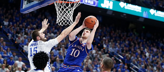 Kansas guard Sviatoslav Mykhailiuk (10) is fouled on the shot by Kentucky forward Isaac Humphries (15) during the first half, Saturday, Jan. 28, 2017 at Rupp Arena in Lexington, Kentucky.
