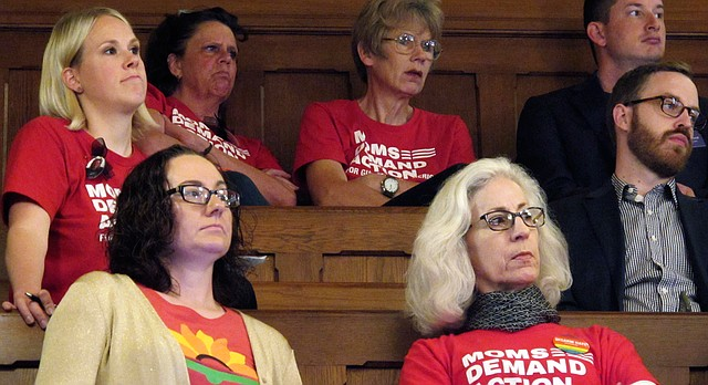 Members of the Moms Demand Action group, wearing red t-shirts, watch a Kansas Senate debate on a concealed carry bill from the chamber's gallery, Thursday, June 1, 2017, at the Statehouse in Topeka, Kan. The group favors keeping concealed weapons out of public hospitals and off university campuses, which Kansas law is set to allow starting in July. (AP Photo/John Hanna)