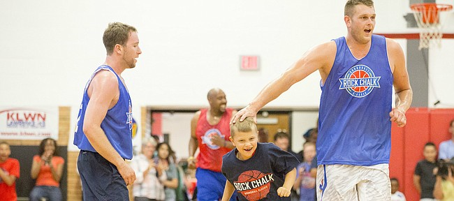Blue team member Cole Aldrich pats teammate Cooper Woestendick, 7, of Olathe, on the head as they run down the court after Cooper scored a basket during the annual Rock Chalk Roundball Classic, played Thursday evening at Lawrence High. The annual basketball game, which features former Kansas players, benefits local kids fighting cancer and other diseases.