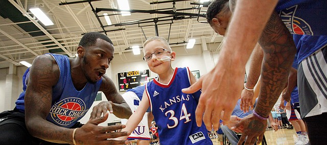 Tyshawn Taylor greets Dagen Korynta, 7, as Dagen runs through a lineup of former KU players during the 2017 Rock Chalk Roundball Classic Thursday evening at Lawrence Free State High School. The annual charity event benefits local families fighting cancer. Dagen was diagnosed with cancer in 2015. As of January 2017, Dagen is in remission.