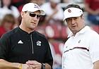FILE — Kansas head coach David Beaty, left, and former Oklahoma head coach Bob Stoops, right, talk before the start of an NCAA college football game in Norman, Okla., Saturday, Oct.29, 2016. (AP Photo/Alonzo Adams)