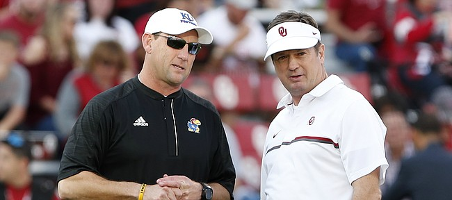 FILE — Kansas head coach David Beaty, left, and former Oklahoma head coach Bob Stoops, right, talk before the start of an NCAA college football game in Norman, Okla., Saturday, Oct.29, 2016. (AP Photo/Alonzo Adams)