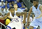 Kansas guard Elijah Johnson pushes the ball up the court against North Carolina guard Reggie Bullock during the second half, Sunday, March 24, 2013 at the Sprint Center in Kansas City, Mo.