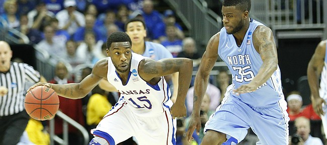 Kansas guard Elijah Johnson pushes the ball up the court against North Carolina guard Reggie Bullock during the second half, Sunday, March 24, 2013 at the Sprint Center in Kansas City, Mo.