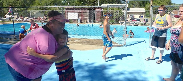 Country Club Swim Club pool manager Missi Pfiefer gives Sam Emert a hug as he arrives Sunday at the pool. Sam thought up an April lemonade stand fundraiser for the pool in which he and six kindergarten classmates in his Raintree Montessori School raised $389 to donate to the pool.