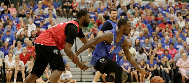 Elijah Johnson, left, tries to hold back Tyshawn Taylor on a fast break during the 2017 Rock Chalk Roundball Classic Thursday evening at Lawrence Free State High School. The annual charity event benefits local families fighting cancer.