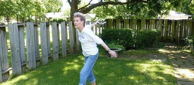 Wynne Mihura shows off her horseshoe pitching form Monday in her yard. On June 14 in Birmingham, Ala., Mihura won a gold medal in the 90-to-94 age group. It was her first competition since breaking her wrist more than a year ago.