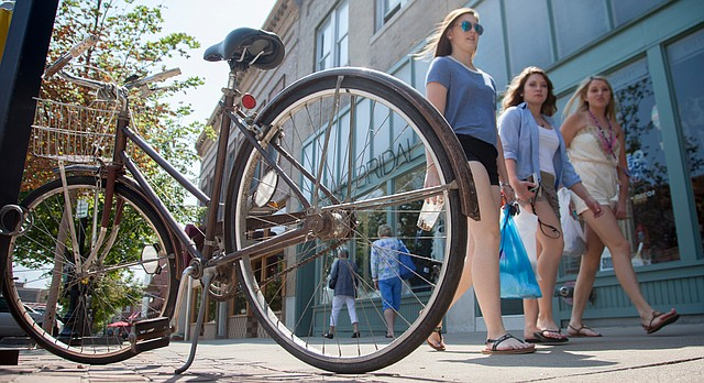 This file photo from August 2015 shows a bicycle parked on the sidewalk near a parking meter in downtown Lawrence.