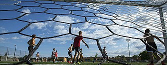 Lawrence High players gather near the goal as they await a corner kick to play out during a summer workout on Friday, June 23, 2017 at LHS.