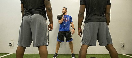 New KU football strength coach Zac Woodfin prepares to lead a warmup session with kettlebells prior to weightlifting at the Anderson Family Football Complex on Thursday, June 29, 2017.