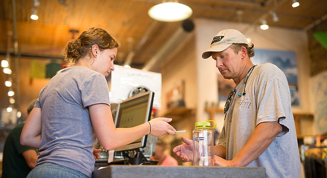 Sunflower Outdoor and Bike Shop manager Sara Bilhimer hands a receipt to Nate Penny, of Lawrence, after a purchase on Thursday, July 6, 2017, at the downtown Lawrence store. A city proposal seeks to renew a .55 percent sales tax that applies to all purchases citywide to fund infrastructure, transit and affordable housing. Opponents of the renewal believe it will disproportionately affect low-income residents.
