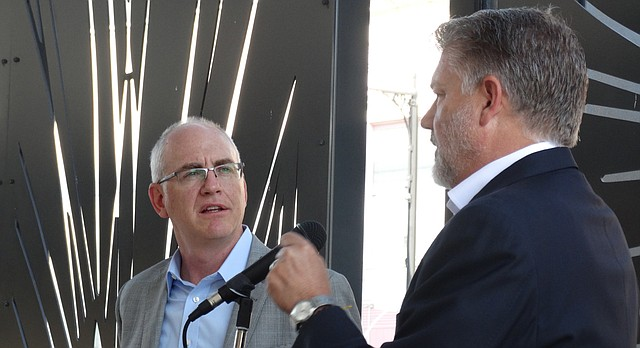 Westar Energy president and CEO Mark Ruelle, right, and Terry Bassham, chairman and CEO of Great Plains Energy and Kansas City Power and Light, announce their companies have agreed to a revised merger plan during a news conference Monday outside Westar's Topeka headquarters.