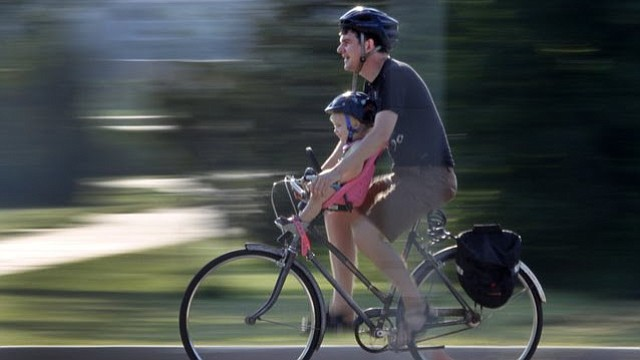 A father and daughter participate in the Lawrence Community Bike Ride Saturday, July 19, 2014.  The ride was hosted by the Lawrence Central Rotary Club and offered three rides of 10, 3 and 1 mile.