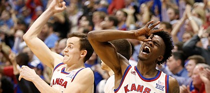 Kansas guard Lagerald Vick (2) and Kansas forward Mitch Lightfoot (44) celebrate a late, second-half three by Kansas guard Devonte' Graham (4), Monday, Feb. 13, 2017 at Allen Fieldhouse.