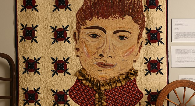 """A portrait of a slave Maria Rodgers Martin, born in 1831, sits on a bed that is made with one of her quilts, Dec. 15, 2015, at the African American Quilt Museum and Textile Academy, 2001 Haskell Ave. Behind the bed on the wall hangs a quilt, """"A Tribute to Maria Rodgers Martin"""" made as a collaborative effort by artists Marla Jackson, Tonia Johnson and several students."""