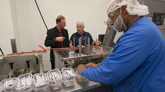 In this file photo from 2014, Marvin Hunt, left, director of the Dwayne Peaslee Technical Training Center, gets some training from Tim Woodroof, physicality maintenance manager, center, as employee Maurice Murphy, right, works a packing machine at the Plastikon Industries Inc. located in the East Hills Industrial Park.