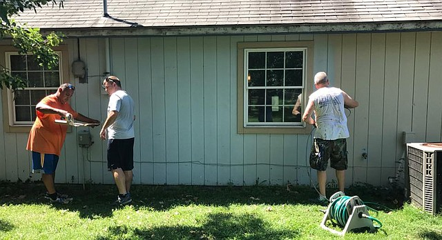 Volunteers organized by the Lawrence Professional Firefighters Charitable Foundation work on the Lawrence house of Irma Blair. Blair is the widow of Mark Blair, a Lawrence firefighter who was killed on duty in 1986.