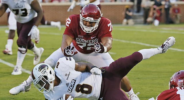 Louisiana Monroe wide receiver De'Vonte Haggerty (8) is brought down by Oklahoma defensive end Amani Bledsoe (72) and linebacker Caleb Kelly (19) during an NCAA college football game between Louisiana Monroe and Oklahoma in Norman, Okla., Saturday, Sept. 10, 2016. (AP Photo/Sue Ogrocki)