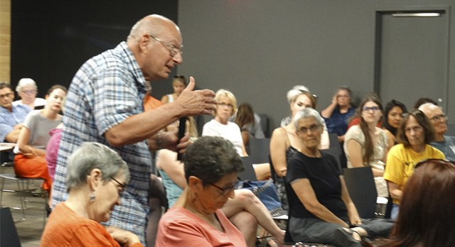 Lawrence resident Joe Harkins speaks in favor of national health insurance during a town hall meeting on health care Thursday at the Lawrence Public Library.