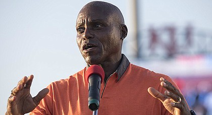 Olympic gold medalist Carl Lewis speaks to Junior Olympic athletes at Rock Chalk Park on Tuesday night during the opening ceremonies.