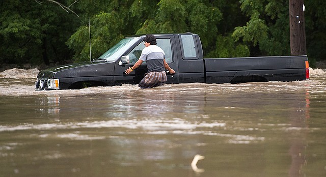 A man tries to get back into the vehicle to have it pulled out after it got stuck in high water in South Kansas City, Mo., on Thursday, July 27, 2017. Overnight storms with heavy rains led to major flooding across the Kansas City area. (Tammy Ljungblad/The Kansas City Star via AP)