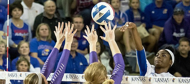 Junior Right Side Hitter Kelsie Payne strikes the ball over the Kansas State defenders, Macy Flowers (12) and Alyssa Schultejans (3), Wednesday night in the Horejsi Center.