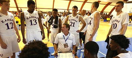 Kansas University's head coach Bill Self, center, gives suggestions to his players during a pause of a basketball game against HSC Roma in Rome, Wednesday, Aug. 2, 2017. (AP Photo/Riccardo De Luca)