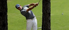 Gary Woodland hits from the trees on the 18th hole during the first round of the PGA Championship golf tournament at the Quail Hollow Club Thursday, Aug. 10, 2017, in Charlotte, N.C. (AP Photo/John Bazemore)