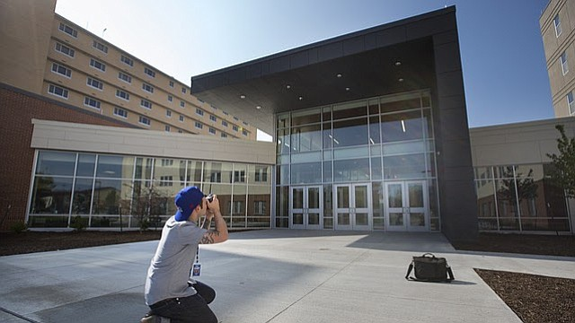 A University of Kansas photographer shoots a photo of the entryway to Downs Hall, which connects the newly-constructed residentce hall with Oliver Hall, Friday, Aug. 11, 2017.