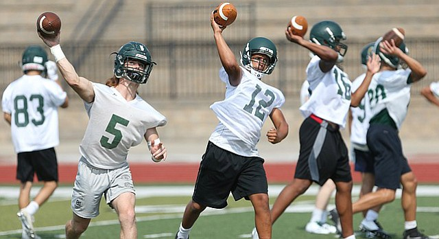 Gage Foster (5), Jordan Preston (12) and a line of Free State quarterbacks throw during practice on Monday, Aug. 14, 2017 at the high school. Monday was the first day for football practice.