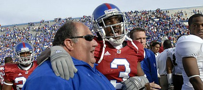 Kansas cornerback Aqib Talib walks off the field with his arm around head coach Mark Mangino following the Jayhawks' 20-15 win over Colorado Saturday at Memorial Stadium. Talib pulled in two interceptions during the 'Hawks win.