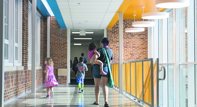 Visitors to a Pinckney Elementary School open house Tuesday walk a new hallway at the school that shows the former brick exterior of the building.