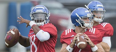Kansas quarterbacks Tyriek Starks, left, Peyton Bender and Carter Stanley throw to receivers during practice on Monday, Aug. 14, 2017 at the grass fields adjacent to Hoglund Ballpark.