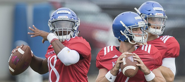 Kansas quarterbacks Tyriek Starks, left, Peyton Bender and Carter Stanley throw to receivers during practice on Monday, Aug. 14, 2017 at the grass fields adjacent to Hoglund Ballpark.
