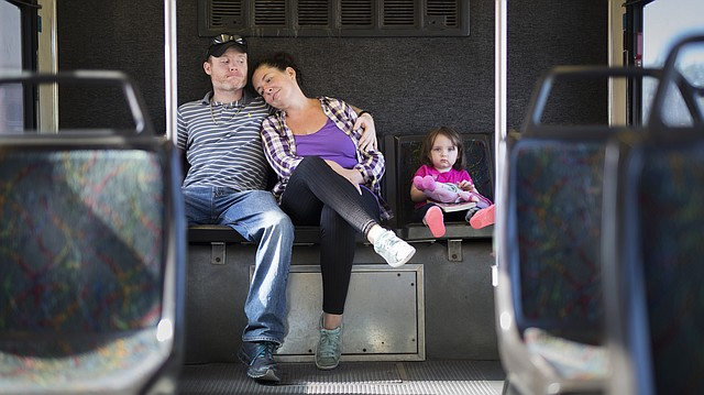 Lawrence residents James and Alicia Womack and their 2-year-old daughter Adrianna wait for their bus to depart from the downtown bus hub at Seventh and Vermont streets on Thursday, Aug. 17, 2017. The renewal of the transit sales tax will be on the November ballot. The tax provides more than 40 percent of the revenue needed to operate the T.