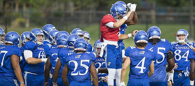 Kansas quarterback Carter Stanley gives a flying bump to running back Kendall Morris, obscured, as the Jayhawks gear up for practice on Friday, Aug. 18, 2017 at the grass fields adjacent to Hoglund Ballpark.