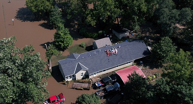 Overland Park Fire Department officials wait for floodwaters to recede before attempting to rescue a family stranded on the roof of their home in Overland Park, Kan., on Tuesday, Aug. 22, 2017. Several roadways in the Kansas City area are flooded and blocked off to traffic after overnight rains pounded the region. The flooding has prompted numerous rescues of stranded motorists and others who scrambled to safety on rooftops. (Rich Sugg /The Kansas City Star via AP)