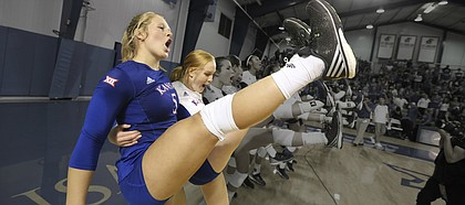 Cassie Wait, left, and Allie Nelson, right, give a high leg kick while singing the Alma Mater after beating the Longhorns in five sets on Saturday, Oct. 29, 2016 at the Horejsi Center.