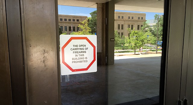 Signs stating that the open carry of firearms is prohibited inside buildings are posted on doors throughout the University of Kansas campus. This sign, on Wescoe Hall, is pictured July 7, 2017.